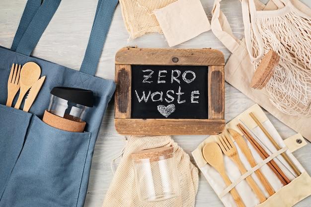 Płaski układ zestawu zero waste. zestaw ekologicznych bambusowych sztućców, bawełniana torba z siateczki, kubek do kawy wielokrotnego użytku, szczotki i butelka na wodę. zrównoważony, etyczny, wolny od plastiku styl życia. widok z góry