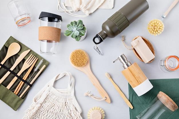 Płaski układ zestawu zero waste. zestaw ekologicznych bambusowych sztućców, bawełniana torba z siateczki, kubek do kawy wielokrotnego użytku, szczotki, mydło w kostce i butelka na wodę. zrównoważony, etyczny, wolny od plastiku styl życia