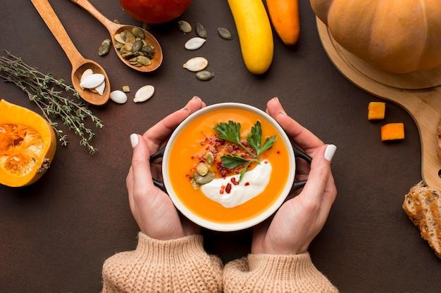 Płaski układ zimowej zupy z dyni w misce trzymanej w rękach