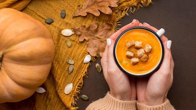 Płaski układ zimowej zupy z dyni z grzankami w kubku trzymanym w rękach