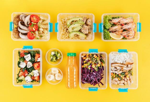 Płaski układ zorganizowanych plastikowych pojemników na żywność z posiłkami
