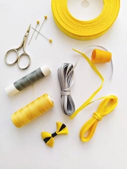 Płaski układanie z zestawem do szycia i akcesoriami do szycia w trendach rozświetlające żółte i ostateczne szare kolory wstążki