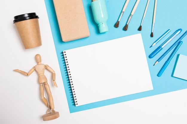 Płaski widok biurka z kreatywnym rozmieszczeniem materiałów biurowych i notatników na pulpicie