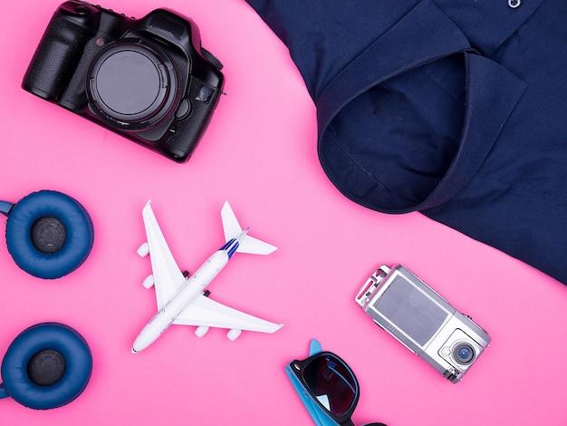 Płaski widok z góry akcesoriów fotografa podróżnika na różowym tle. aparat fotograficzny, okulary przeciwsłoneczne. słuchawki. koszula