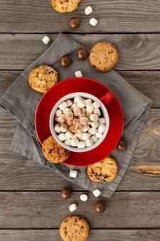 Płaski widok z góry gorąca czekolada z pianką marshmallow w czerwonym kubku na drewnianym stole