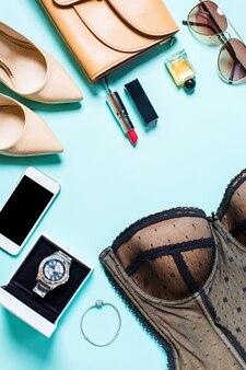 Płaski widok z góry, makiety damskie seksowne ubrania i akcesoria na turkusowym tle. telefon, okulary przeciwsłoneczne, bransoletka