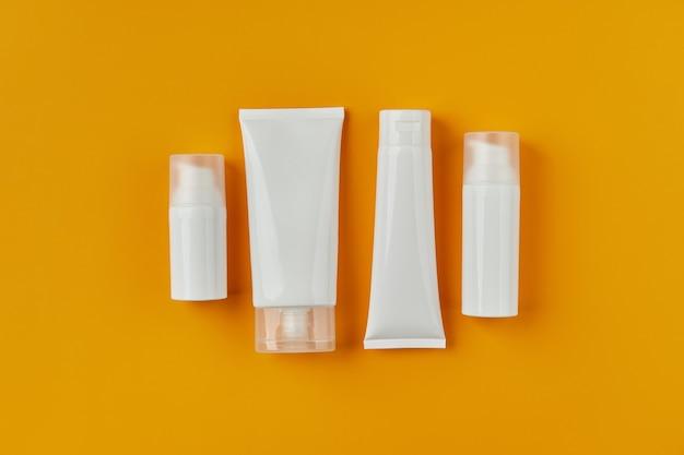 Płaski widok z góry puste białe tubki butelki z produktami do pielęgnacji skóry na pomarańczowym tle kreatywnych