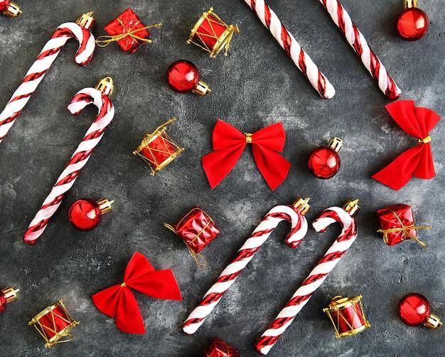 Płaski wzór z świątecznego wystroju, pudełka na prezenty, czerwone kokardy, bombki, słodycze.