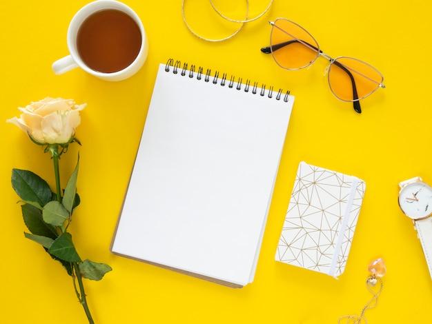 Płaski zestaw kobiecego biurka z makietą notatnika, kwiatem róży i filiżanką herbaty. skopiuj makietę miejsca na żółtym tle.