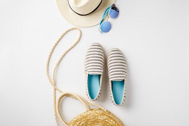 Płaskie akcesoria podróżne z kapeluszem słomkowym, letnimi butami, torbą i okularami przeciwsłonecznymi.