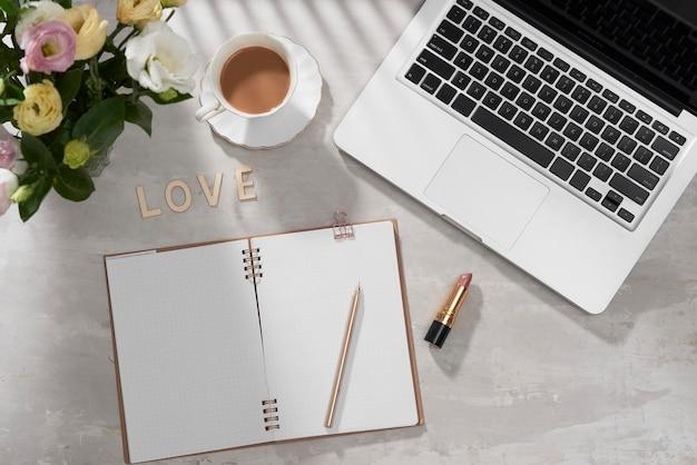 Płaskie biurko do domowego biura. kobiecy obszar roboczy z laptopem, różowym bukietem lisianthus, szminką, pamiętnikiem i listem miłosnym na białym tle