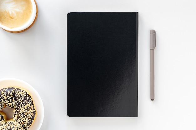 Płaskie biurko do pracy, czarny notatnik, długopis, kawa i czekoladowy pączek