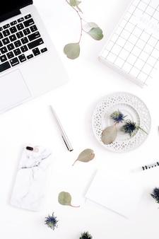 Płaskie biurko do pracy w domu z laptopem, telefonem komórkowym z marmurową obudową, długopisem, papierem, notatnikiem i gałęziami eukaliptusa na białym tle