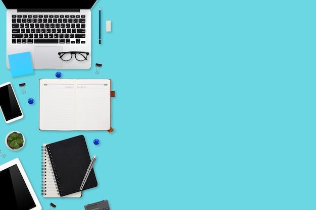 Płaskie biurko stół roboczy z laptopem, artykułami biurowymi, filiżanką kawy, tabletem i smartfonem mobilnym na kolorowym tle