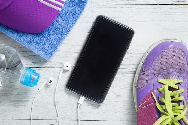 Płaskie buty sportowe, smartfony i sprzęt treningowy.