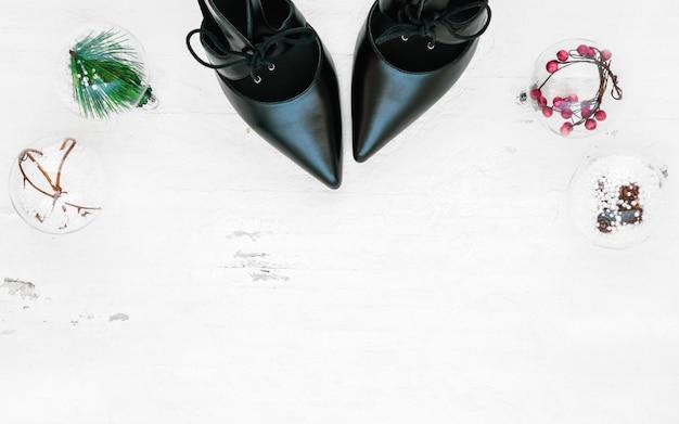 Płaskie, czarne buty na obcasie, mini choinka i ozdoby świąteczne