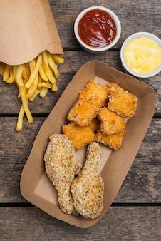 Płaskie frytki ze smażonym kurczakiem i sosami