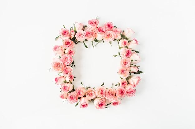 Płaskie kwadratowe obramowanie ramki z makietą pustej przestrzeni kopii wykonanej z różowych pąków kwiatowych róży na białej powierzchni