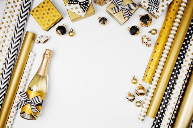 Płaskie lay boże narodzenie lub tło strony z pudełkami prezentowymi, butelką szampana, kokardkami, dekoracjami i papierem do pakowania w kolorach złotym i czarnym. płaski układanie, widok z góry