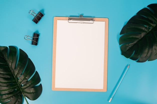 Płaskie lay makieta papieru a4 ze schowka, liści palmowych i ołówek na niebieskim tle.