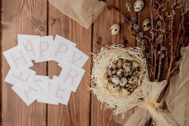 Płaskie lay skład jaj przepiórczych i karty z tekstem wesołych świąt na drewnianym stole. widok z góry.