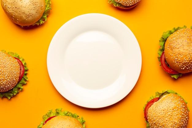Płaskie leżące hamburgery z pustym talerzem