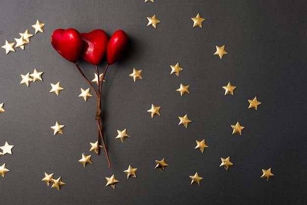 Płaskie leżące zdjęcie żółtych gwiazd i czerwonych serc na czarnym stole