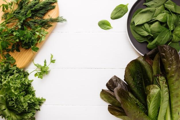 Płaskie leżał z deską do krojenia i miską świeżych liści sałaty zielonej szpinaku i sałaty, rzymskiej i pietruszki, bazylia na białym tle. koncepcja zdrowego odżywiania