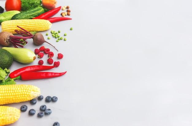 Płaskie leżał z różnymi warzywami, owocami, jagodami, orzechami, przyprawami, ziołami, oliwą z oliwek. skopiuj obszar miejsca na jakiś tekst. warzywa na szarym tle betonu. pojęcie zdrowej żywności ekologicznej bio