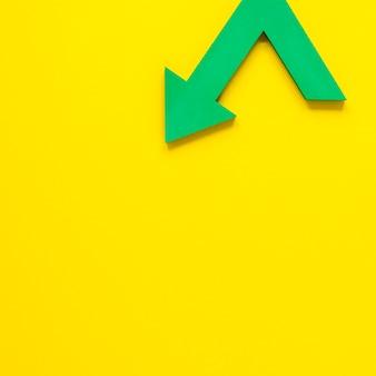 Płaskie leżała zielona strzałka na żółtym tle z kopiowaniem miejsca