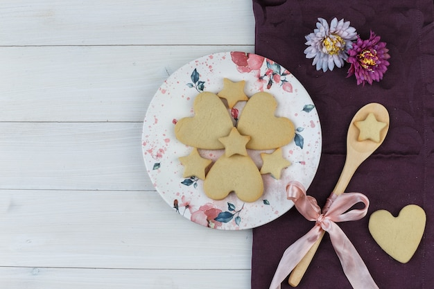 Płaskie leżały ciasteczka w talerz i drewnianą łyżką z kwiatami na tle drewnianych i tekstylnych. poziomy