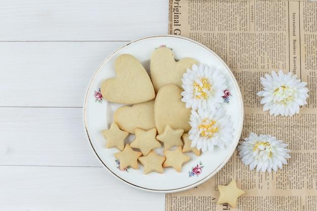 Płaskie leżały ciasteczka w talerz z kwiatami na tle drewnianych i gazet. poziomy