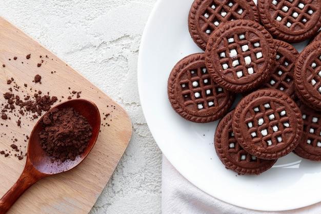 Płaskie leżały ciasteczka z kakao na białym drewnianym stole