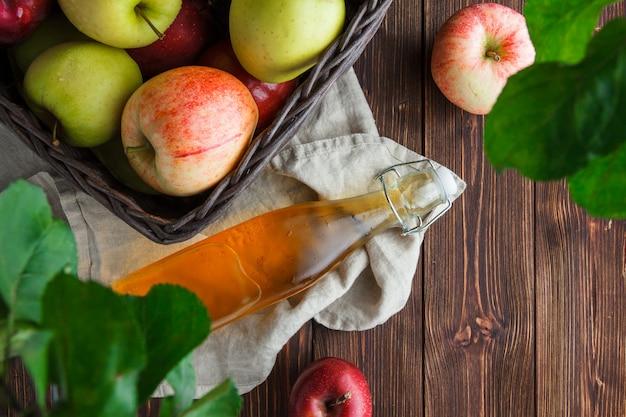 Płaskie leżały jabłka w pudełku z liśćmi i sokiem jabłkowym na tkaninie i drewniane tła. poziomy