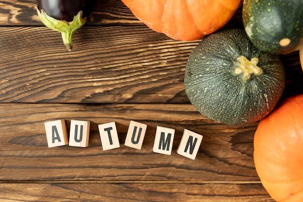 Płaskie leżały kolorowe dynie z napisem jesień