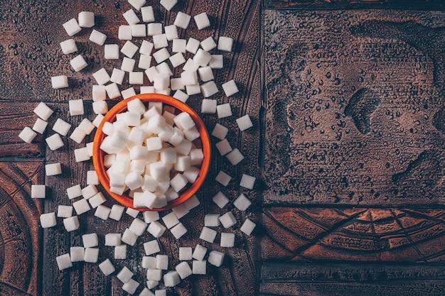 Płaskie leżały kostki cukru białego w pomarańczowej misce na ciemnym drewnianym stole. poziomy