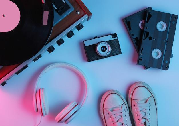 Płaskie leżały obiekty popkultury w stylu retro z lat 80. odtwarzacz winylowy, słuchawki, taśmy wideo, kamera filmowa, trampki z gradientowym neonowo-niebiesko-różowym światłem. fala retro. widok z góry