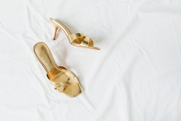 Płaskie leżały złote buty damskie na białej lnie