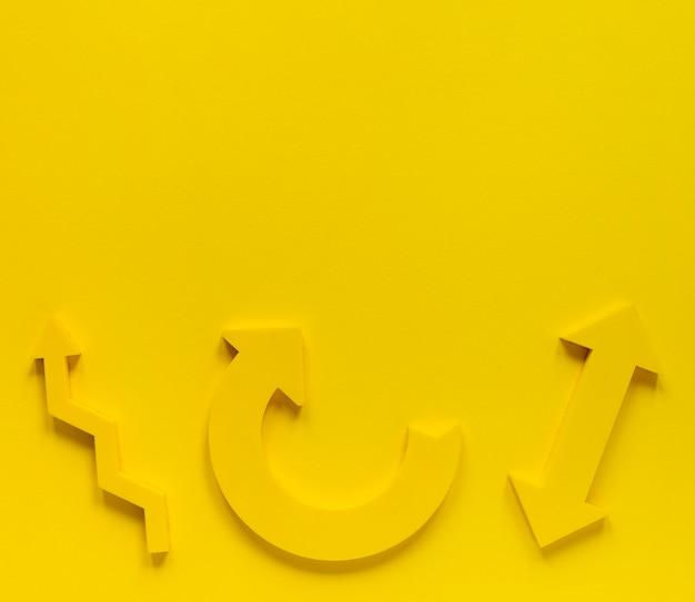 Płaskie leżały żółte strzałki na żółtym tle z kopiowaniem miejsca