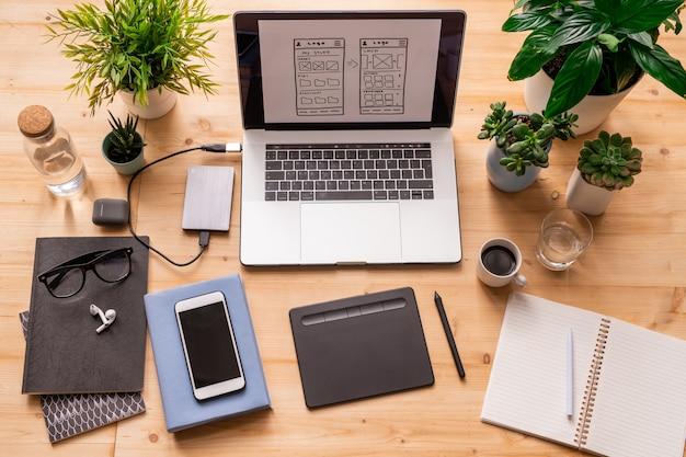 Płaskie miejsce pracy architekta lub projektanta z gadżetami mobilnymi, notatnikami, okularami, roślinami domowymi, butelką wody i napojami