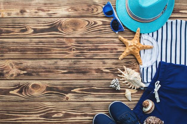 Płaskie nieruchome ubrania dla dzieci. szafa dziecięca. odzież plażowa i wakacyjna dla małego chłopca. tło drewniane