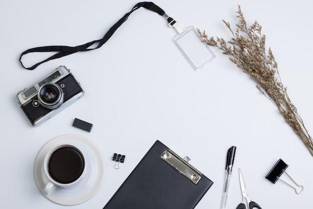 Płaskie, nowoczesne biurko z biurkiem w widoku z góry. kamery kawy i pióra metek na białym tle