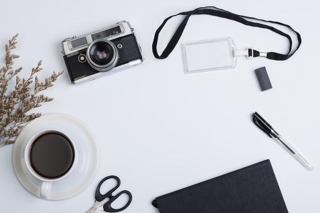 Płaskie, nowoczesne biurko z biurkiem w widoku z góry. książka, aparat fotograficzny, kawa, metek i długopis na białym tle
