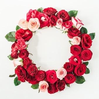 Płaskie obramowanie ramki z makietą pustej przestrzeni kopii wykonanej z różowych i czerwonych kwiatów róży na białej powierzchni