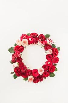 Płaskie obramowanie ramki z makietą pustej przestrzeni kopii wykonanej z różowych i czerwonych kwiatów róży na białym tle