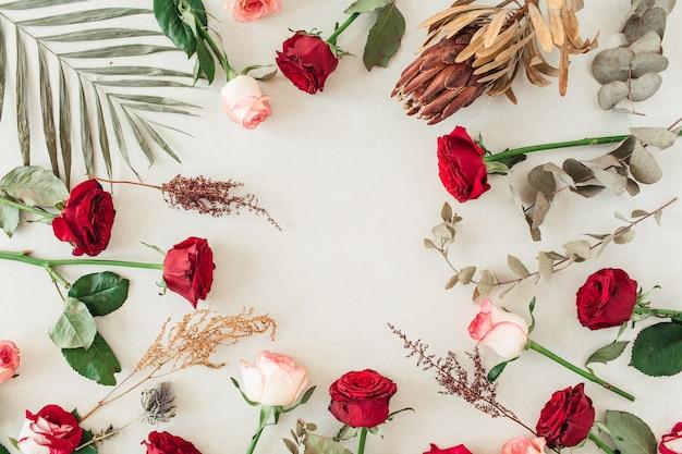 Płaskie obramowanie ramki z pustą makietą przestrzeni kopii wykonanej z różowych i czerwonych kwiatów róży, protea, tropikalnych liści palmowych, eukaliptusa na beżu
