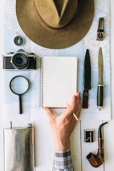 Płaskie planowanie przygody. podróż vintage sprzęt na mapie. podróżnik, odkrywca ręka w ramce, trzymając pusty notatnik. pionowe zwiedzanie, turystyka pustej przestrzeni plakat, pocztówka, szablon.