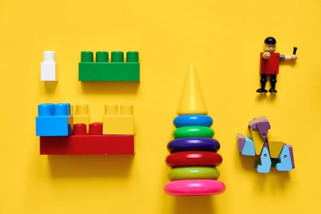 Płaskie, plastikowe i ekologiczne drewniane zabawki. rozwijanie gier. żółty