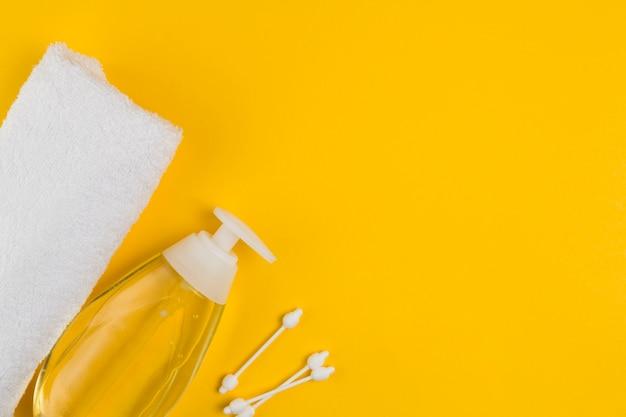 Płaskie położenie dozownika oleju i ręcznika na chrzciny z miejscem na kopię
