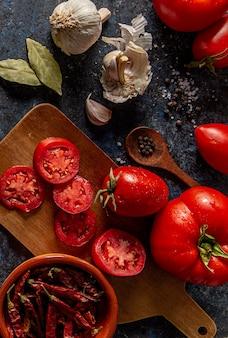 Płaskie pomidory z czosnkiem i liśćmi laurowymi